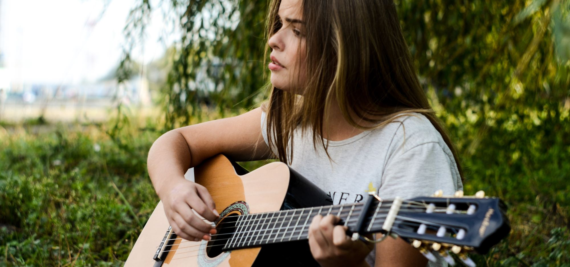 A young dark-haired woman playing acoustic guitar while sitting on grass.